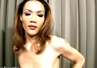 Skinny redhead ladyboy with low hanging balls tugs two cocks